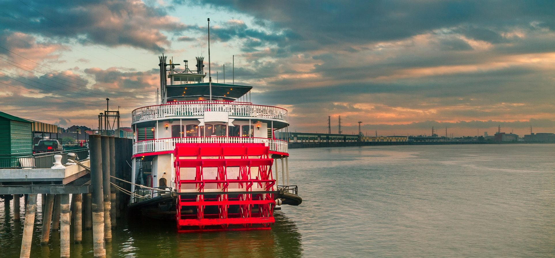 Steamboat docked on the Mississippi River at sunset.