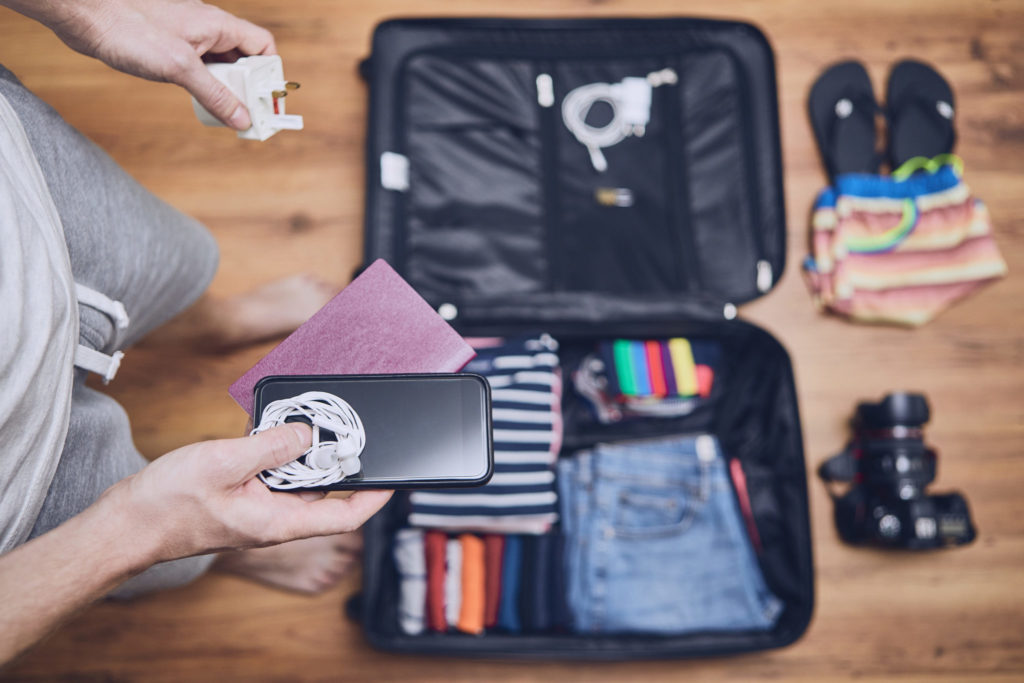 Man packing phone charger into suitcase