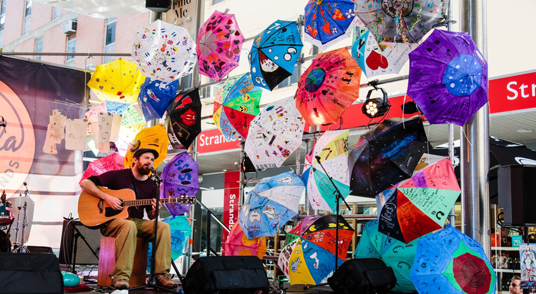 Musician playing guitar surrounded by colourful umbrellas.