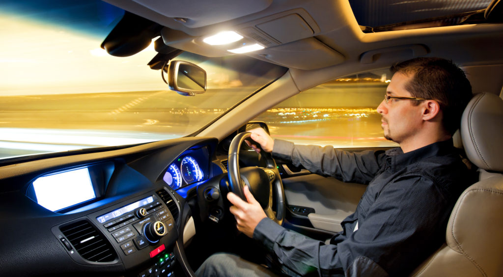 Man driving with interior light on.