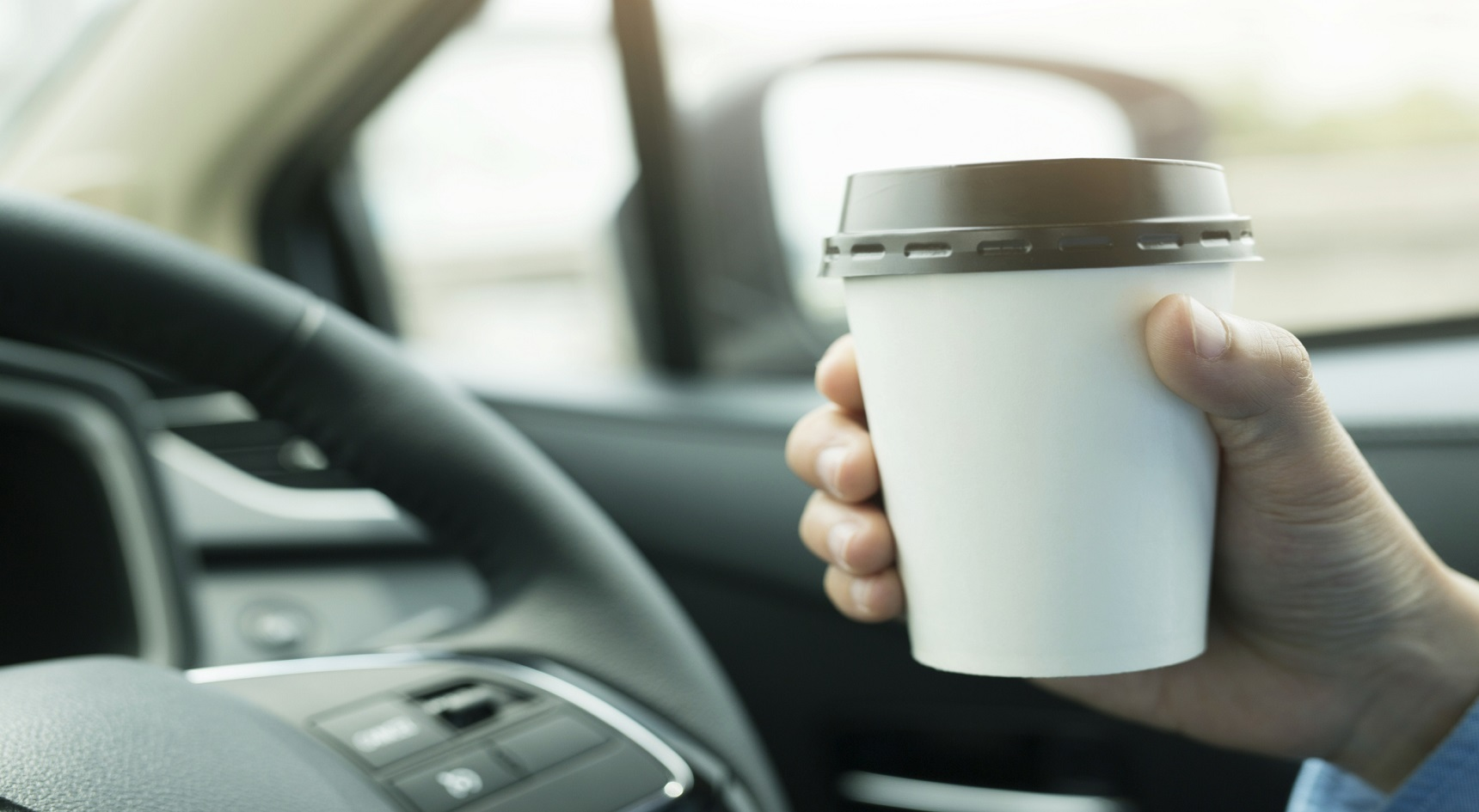 Man's hand holding coffee while driving.