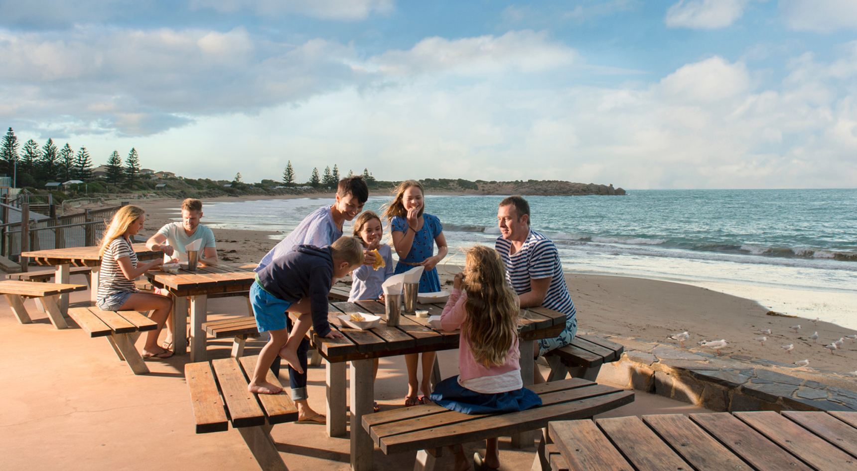 A family sitting around a table eating fish and chips with the beach in the background.