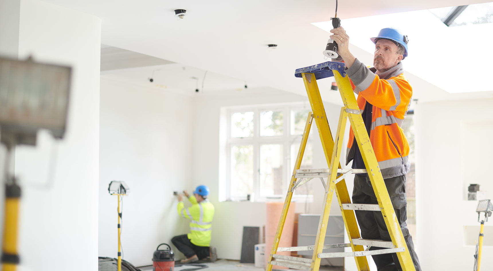 An electrician standing on a ladder installing downlights