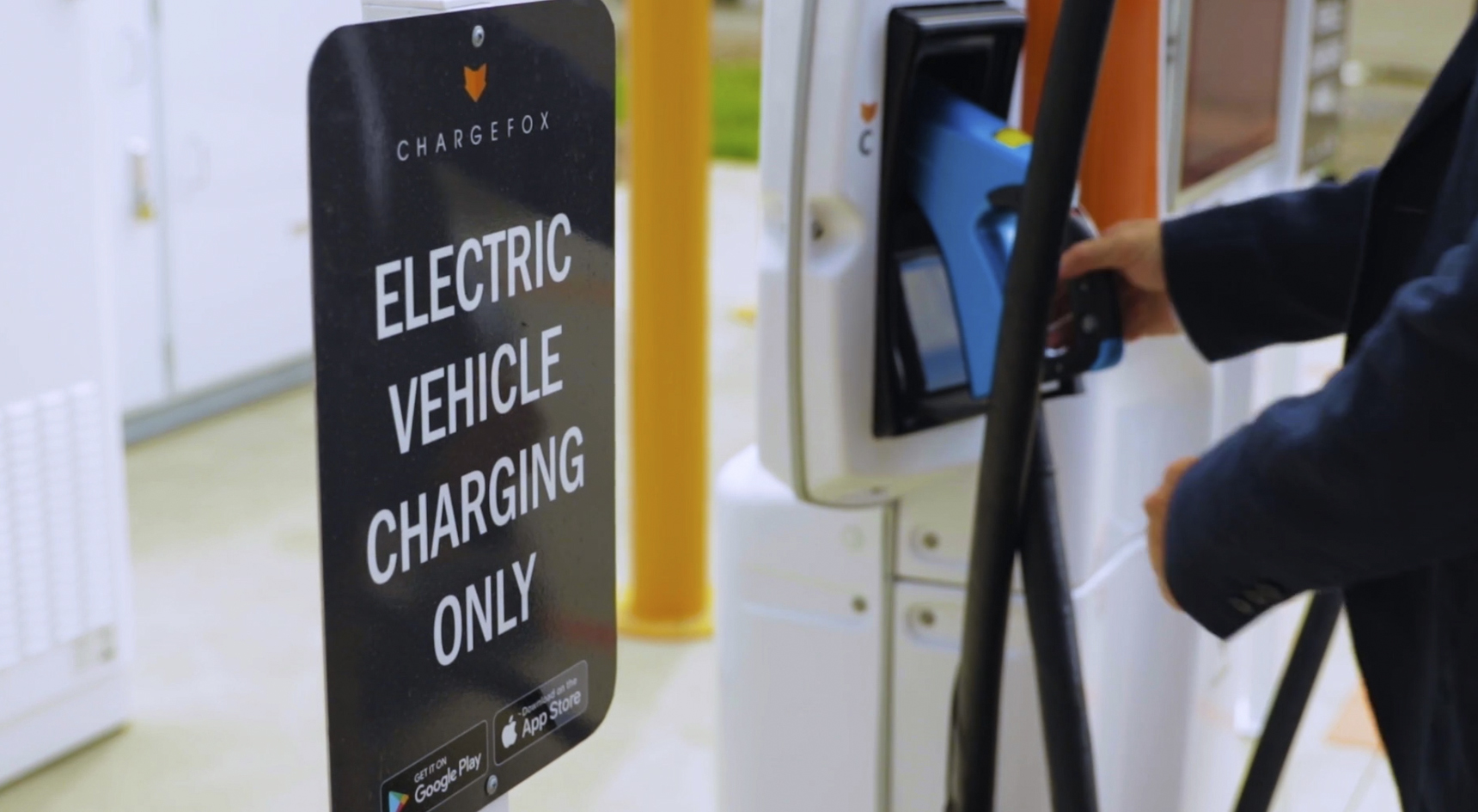 A person's hand reaching for a charger at an Electric Vehicle charging station.